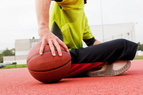 man sitting on the ground with a basketball